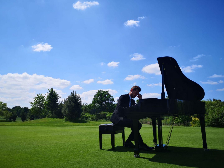 Mężczyzna gra na fortepianie na tle połaci trawy i nieba